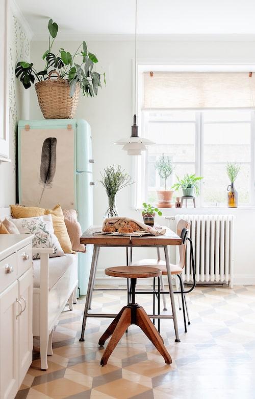 Köket är Marikas favoritplats i hemmet där hon ofta lagar mat eller målar vid köksbordet. Pianostolen är fyndad från Facebook Marketplace. Svart stol med lädersits, Menu Afteroom. Stol Sjuan, Fritz Hansen. Fjäderaffisch, Artilleriet. Lampa PH 3¿-3, Louis Poulsen.