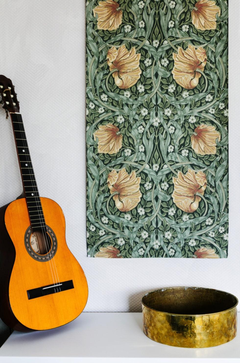 Detaljer. På tv-bänken från Ikea står gitarren lutad. På väggen sitter en bit av en William Morris-tapet. Mässingskålen är från Larssons lager.