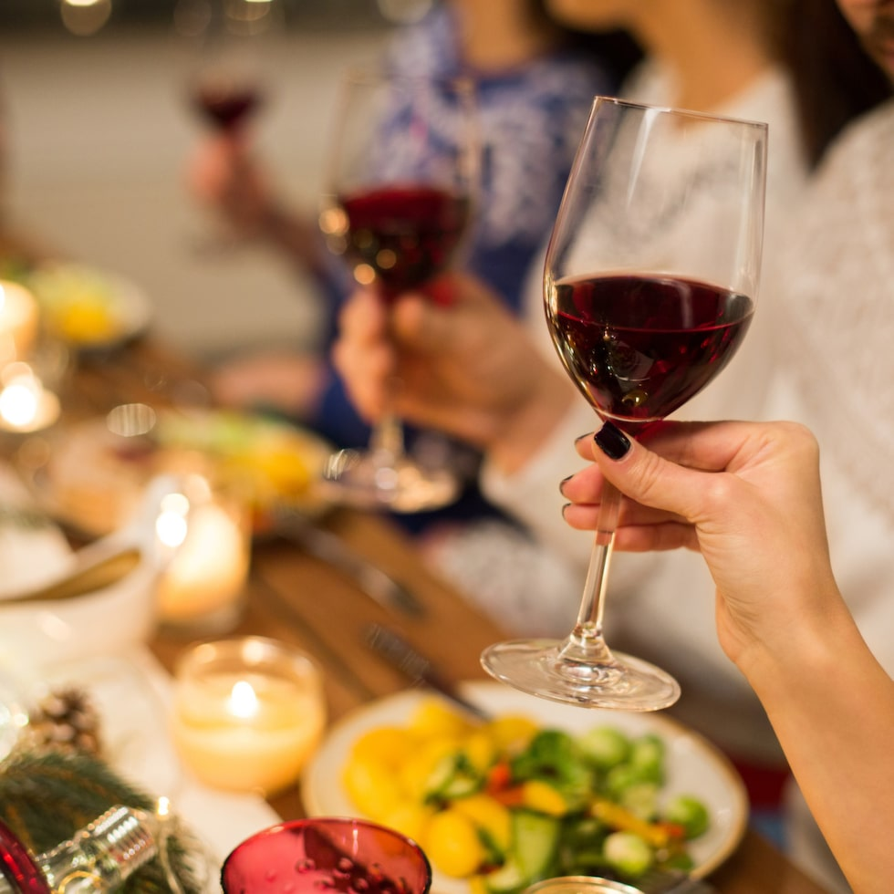 holidays and celebration concept - close up of happy friends having christmas dinner and drinking red wine