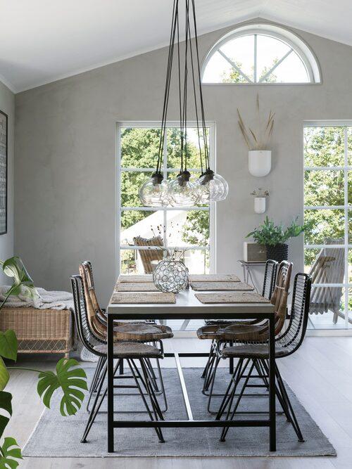 Karin och Janne valde att ha öppet upp till nock för att få rymd i kök och matrum. De stora fönstren och det lilla takfönstret förstärker den luftiga känslan. Matbordet med betongskiva är specialbeställt hos Boehm's för att passa perfekt i mått. Stolar, Affari och House Doctor. Matta, Fondaco. Lampor Bistro, Hallbergs belysning.