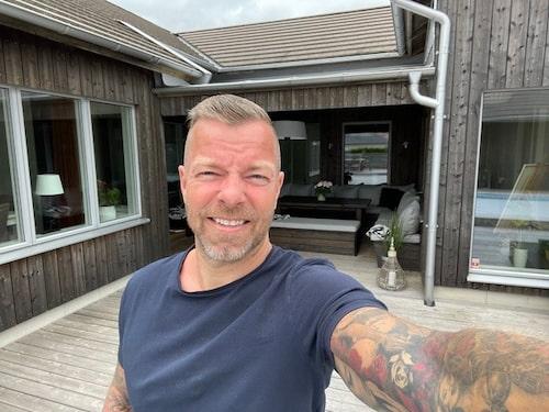 """Casper Janebrink på altanen med uterummet i bakgrunden. Där kopplar han både av och förbereder sig för """"Bingolotto Sommarkväll""""."""