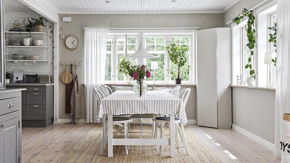 Bra sociala umgängesytor med öppen planlösning mellan kök och matplats samt vardagsrum med öppen spis.
