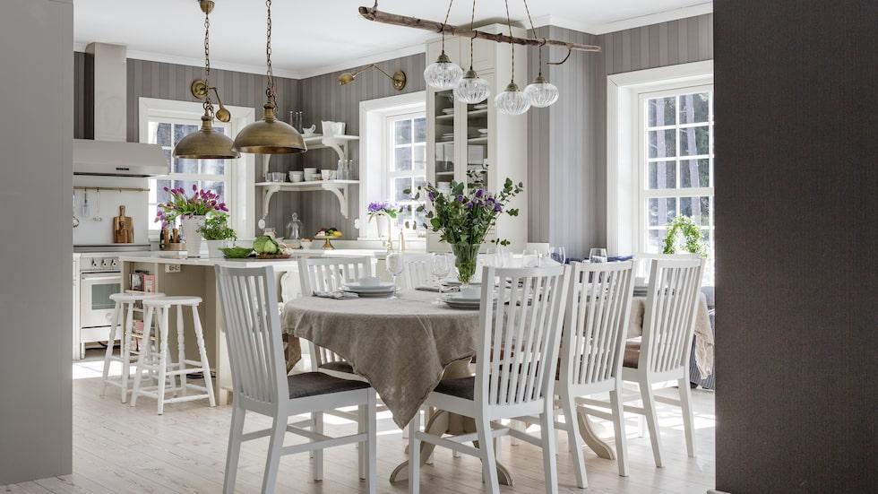 Köket i lantlig New England-stil går i en sober färgskala med egenhändigt byggda shakerinspirerade sparksocklar nertill. Kök, fläkt och beslag, Electrolux Home. Bänkskivorna är av komposit Silence Stone. Tapet från Midbec.