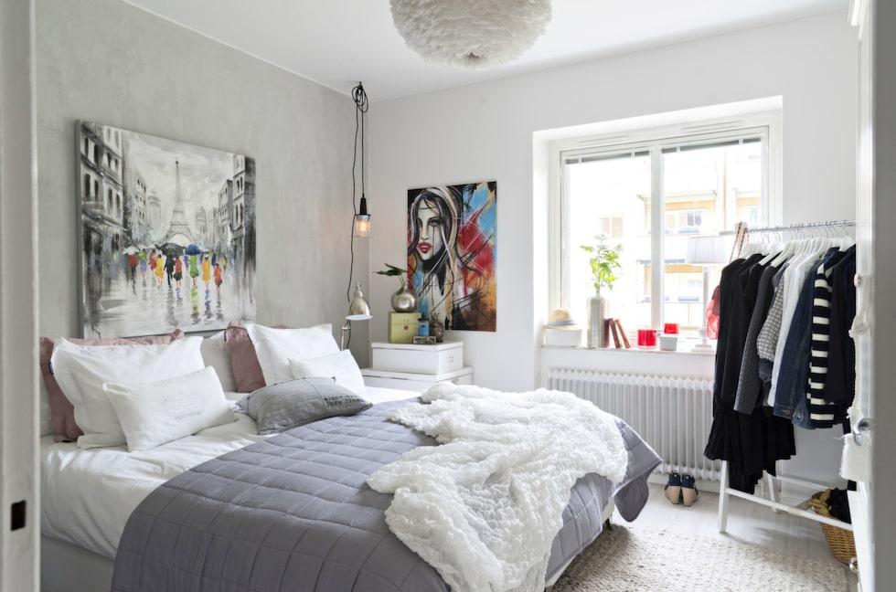 Sovrummet är minimalistiskt inrett i ljusa nyanser för att skapa en rofylld och harmonisk känsla. Lyxiga lakan och kuddar gör rummet varmt och ombonat. Tavlan ovanför sängen kommer från Konstlagret, klädställningen från Mio och överkast från Zebra collection. Tavlan med kvinnan är målad av Kattis Palmnäs. Hängande taklampan i industristil från Clas Ohlson. Vita förvaringslådor från Ikea.