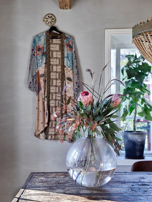 Ett vackert klädesplagg kan bli som en tavla på väggen. Kimono gjord av återvunna indiska sidensaris, Sissel Edelbo. Vasen Pallo, från Skrufs glasbruk.