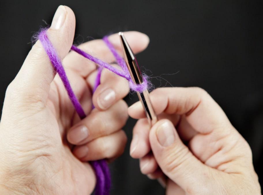 2. Linda slutändan av garnet runt vänster tumme, framifrån och bakåt. Linda garnet från nystanet över pekfingret. Garnändarna håller du sedan fast mot handflatan.
