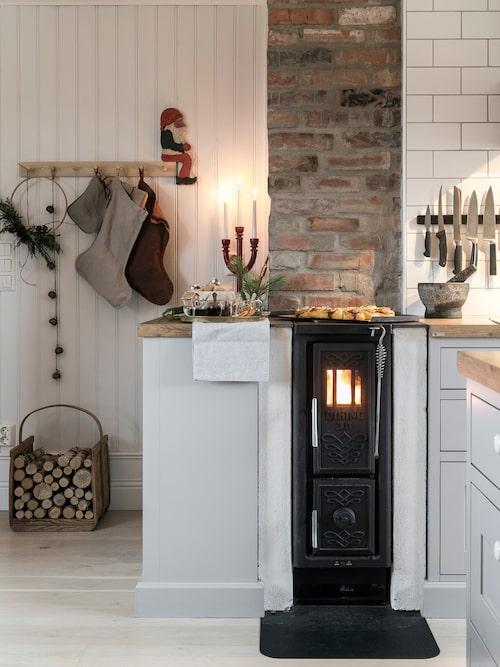 Ida och Kristofer är nöjda med sin kamin, den ger skön värme och en gammaldags karaktär till köket. Att man ser elden är ett plus. Knopplist, Lagerhaus. Julstrumpor, Granit. Vedkorg, ljusstake och tomte, loppis.
