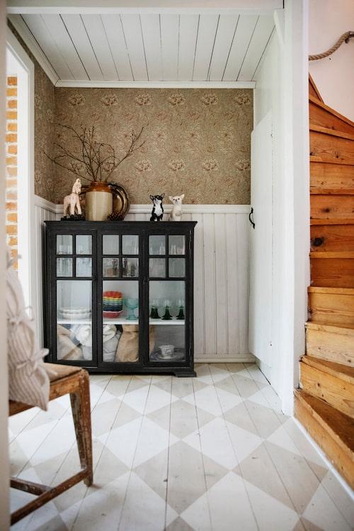 Här kom man tidigare in i stugan. Linnea har målat golvet schackrutigt. Skänken är nyinköpt och målad i en mörkt grå färg. Tapet, William Morris. Skänk, Underbara hem.