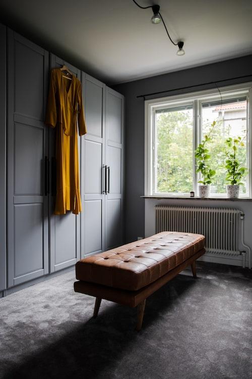 """""""Det här rummet var redan möblerat som en walk-in closet när vi flyttade in. Det är helt vanliga Ikeagarderober som har målats i samma grå nyans som väggen och uppdaterats med Pull bar från Buster + Punch. Bänk från Sofa company."""""""