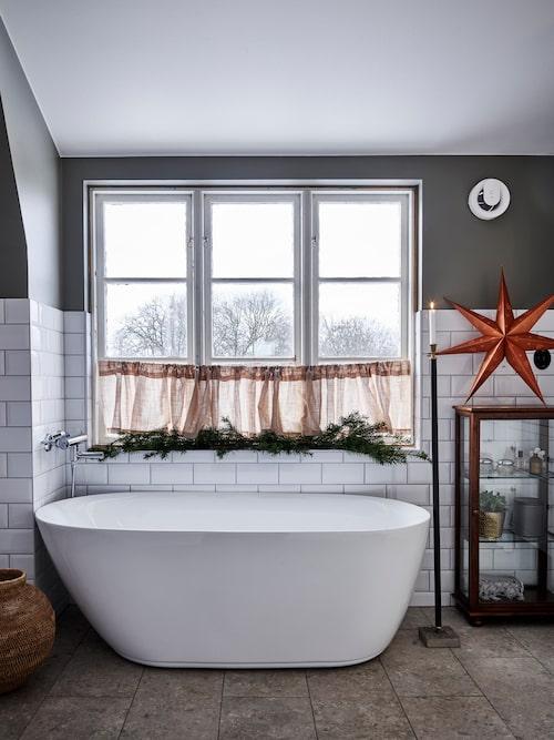Det charmiga badrummet går i gammaldags stil och har ett inbjudande badkar vid fönstret.