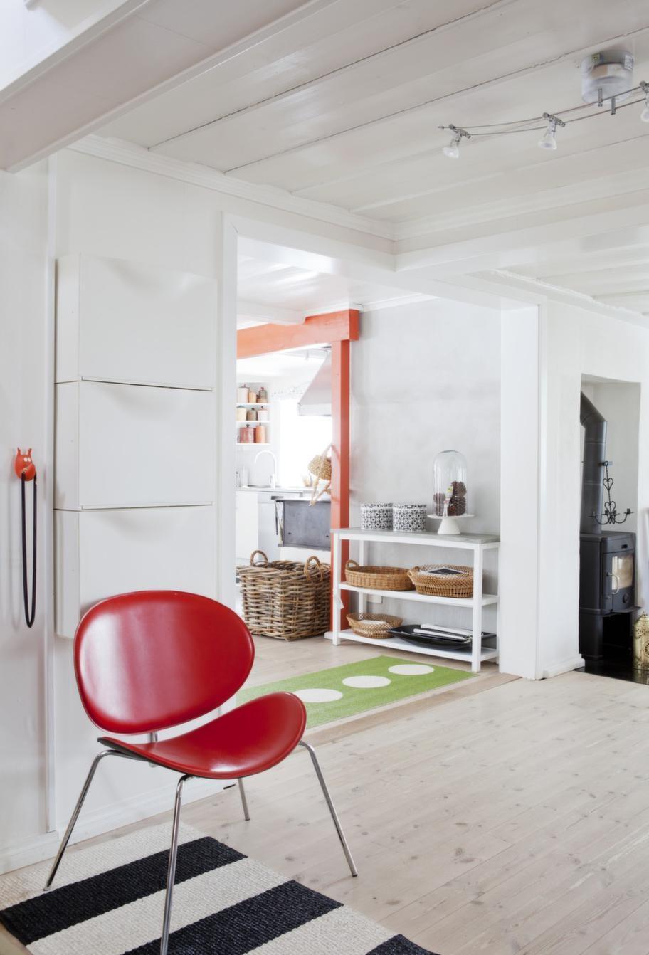 Röda detaljerÖverallt i huset finns färgglada möbler och tyger. Mattor från Pappelina.