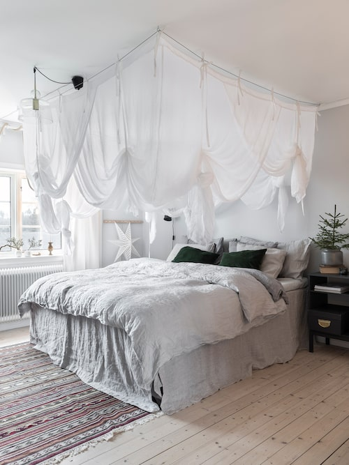 Baldakinen och sängkappan ger sovrummet en ombonad känsla. Baldakin och sängkappa, Ellos. Matta, Ikea. Sängkläder, H&M Home.