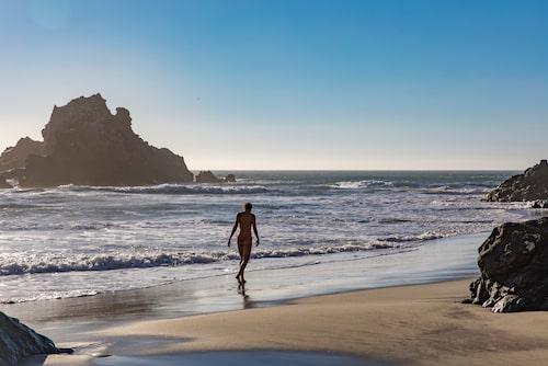 Promenera på mjuk sand på Pfeiffer Beach i Big Sur.