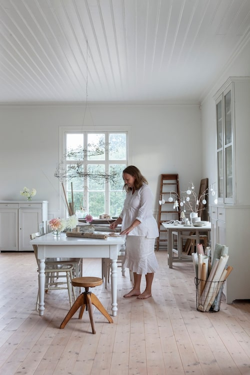 Mari i sin ateljé, ett av de gamla klassrummen med 3.5 meter i takhöjd och stora fönster. Skåpet på höger sida är egentligen två möbler, en skänk och ett vitrinskåp som har staplats på varandra. Möblerna är loppisfynd.