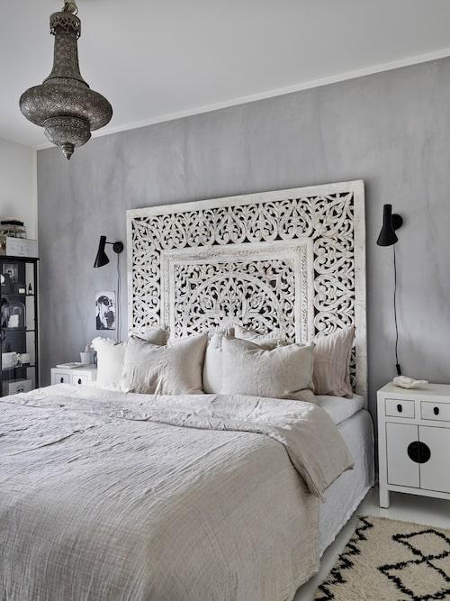 Sänggaveln i parets sovrum är egentligen en tempeltavla från Bali. Väggen bakom är målad med kalkfärg från Kalkitir. Taklampa, auktionsfynd. Sängbord, Bazaar.se. Matta, Day Home. Vägglampor, designade av Arne Jacobsen och inköpta på Lauritz auktioner.