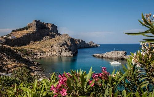 Stranden Saint Paul's ligger vid foten av berget som kröns av Lindos Akropolis.