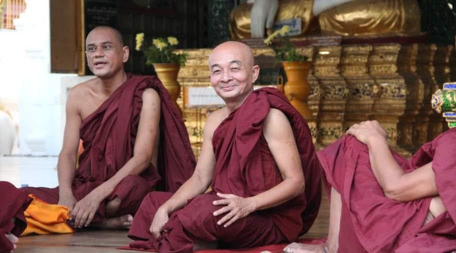 Munkar vilar i skuggan vid Schwedagonpagoden.
