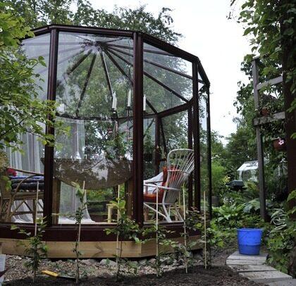 PRYDER SIN PLATS. Lusthuset känns betydligt mer användbart än den gamla brunnen och ger ett verkligt lyft till trädgården. I sommar ska kanten på träplattformen målas i samma faluröda färg som växthuset och de övriga byggnaderna på tomten har.