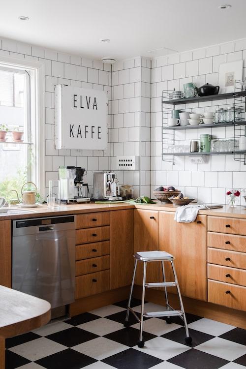 """Själva köket var i bra skick när familjen flyttade in, så de ville göra så lite som möjligt men ändå förstärka funkiskänslan. Golvet byttes, skåp och luckor fick nya handtag och knoppar från Buster + Punch, överskåpen plockades ner och väggarna kaklades för att sedan prydas av Stringhyllor. """"Elva kaffe-lampan har min svärfar gjort, och här i Nässjö är ju elvakaffet lite heligt"""", säger Sofia skämtsamt."""
