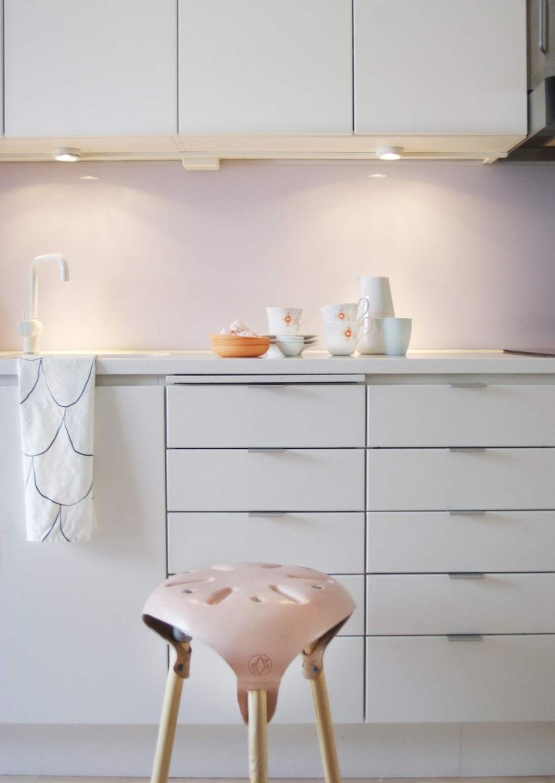 Köket är vitt med en bänkskiva i corian. Handduk från Asplund. Pallen är köpt från ett designkollektiv i Amsterdam.