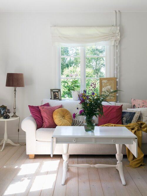 Det ljusa vardagsrummet har vacker utsikt mot trädgården genom de spröjsade fönstren. Färgglada kuddar ger rummet värme. Det antika soffbordet har Jennie målat vitt.