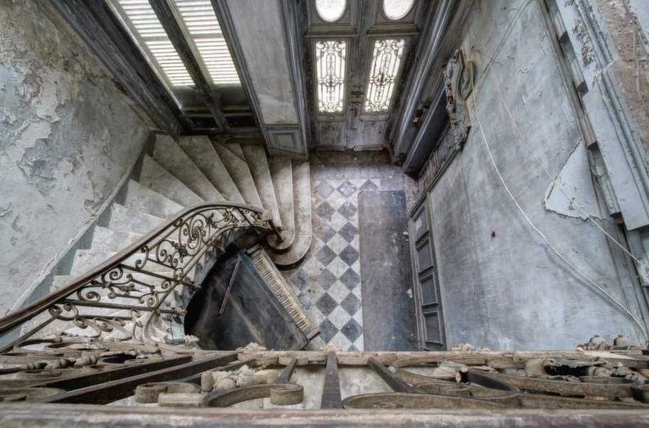 Ett gammalt förfallet piano står fastkilat under stora trappen i den här mangårdsbyggnaden i centrala Frankrike.