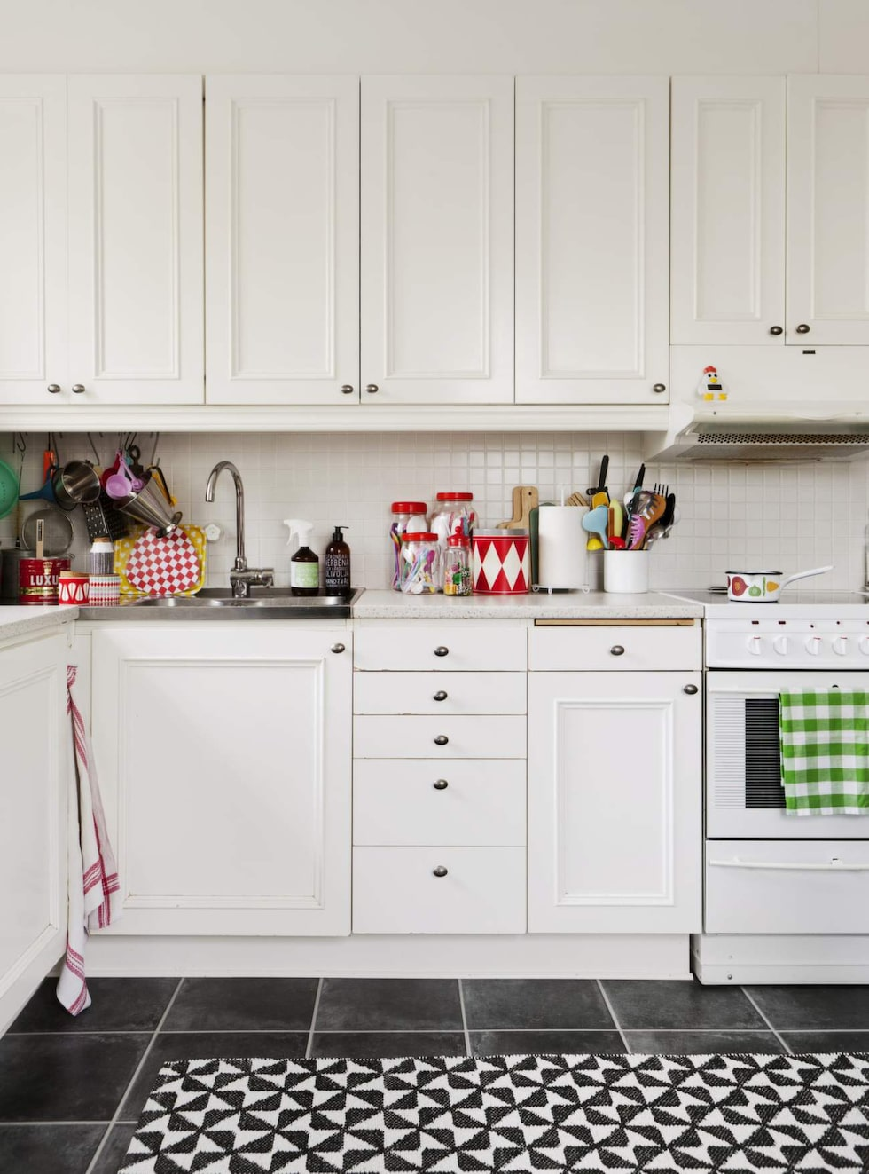 Diverse burkar på köksbänken från loppisar och från egna butiken Glad!. Matta från Olssons tyger.