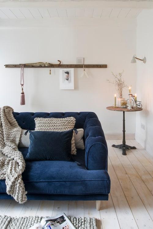 Soffa från brittiska Love your home. Blå kudde med tofs från Linum. Stickad pläd och kudde från Miljögården. Bistrobordet är en gåva. Klädkrok från Vadstena antik.