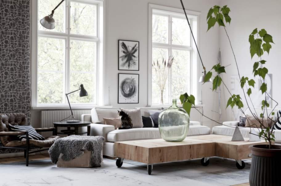 Här finns gott om utrymme att umgås. Sofforna kommer från Ikea och borden har familjen byggt själva. Den stora, gröna flaskan är ett loppisfynd, liksom den sköna skinnfåtöljen från Dux. Tavlorna på väggen är inramade original. Tapten till vänster är ett resultat av ett samarbete med Boråstapeter.