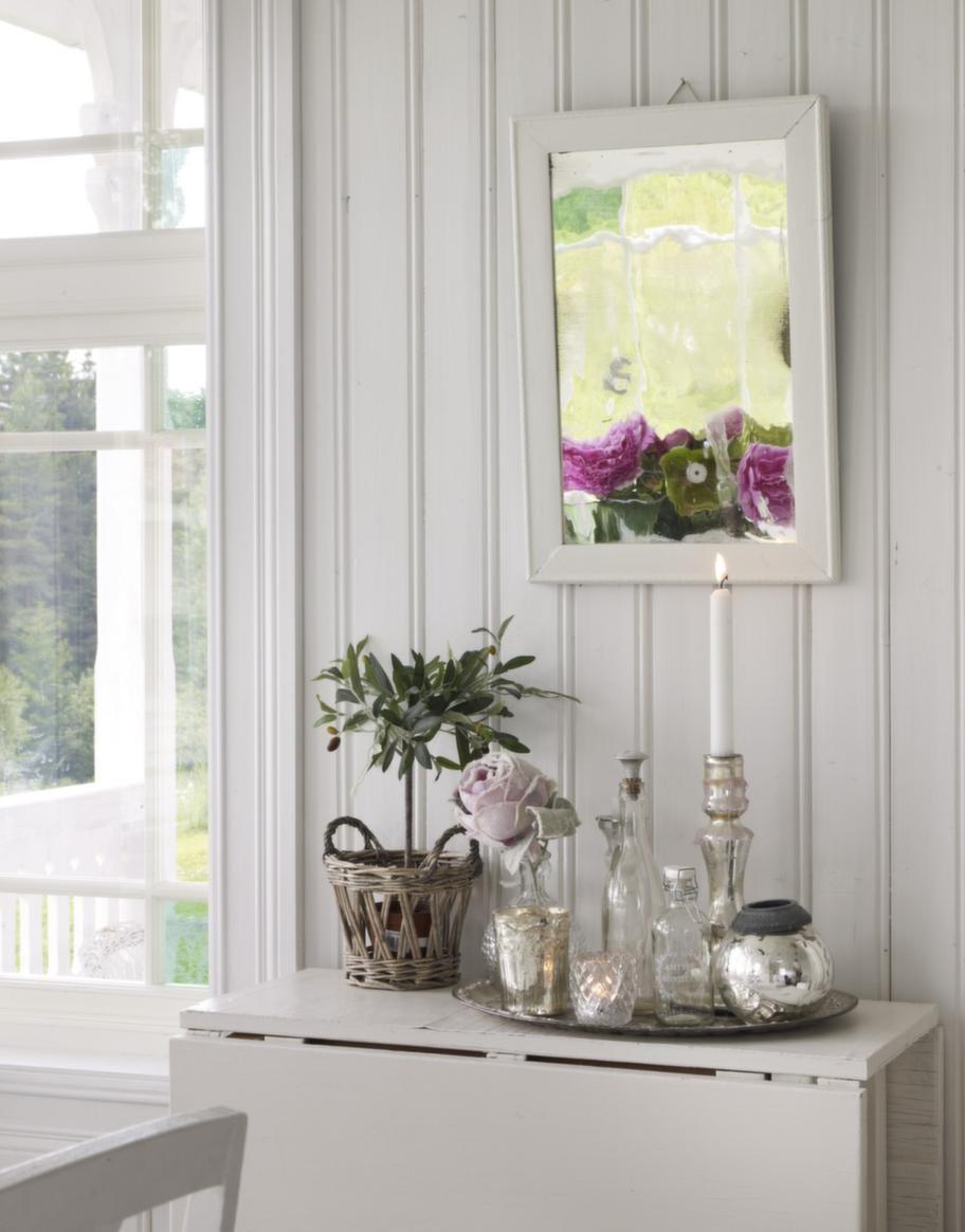 Stilleben. Vackra prydnader i form av ljusstakar och gammaldags parfymflaskor får stå på en bricka under spegeln.