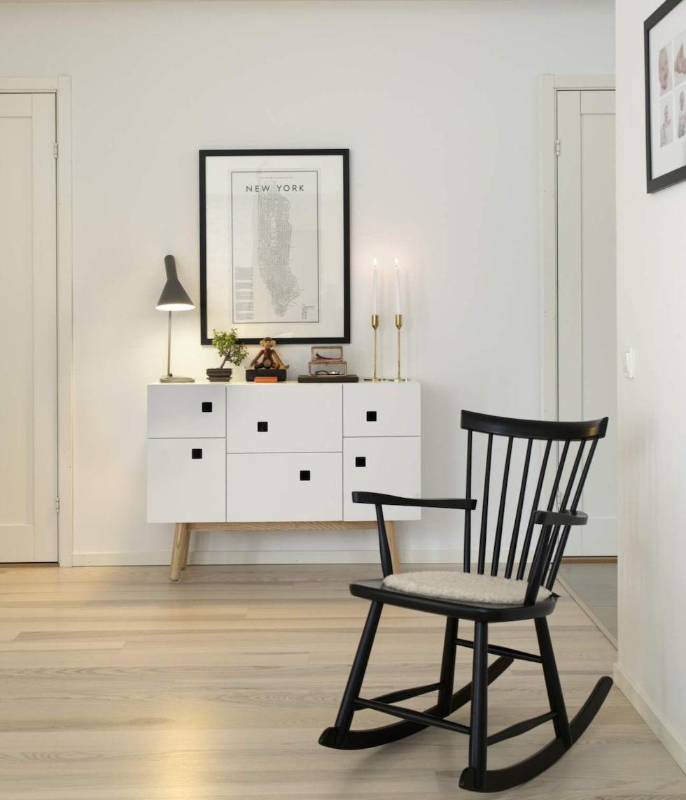 Byrån med sin silrena design i vitt och trä skapar värme i inredningen. Ljusstakar Skultuna, bordslampa, Arne Jacobsen, tavla, David Ehrenstråhle, stol Lilla Åland, Carl Malmsten.