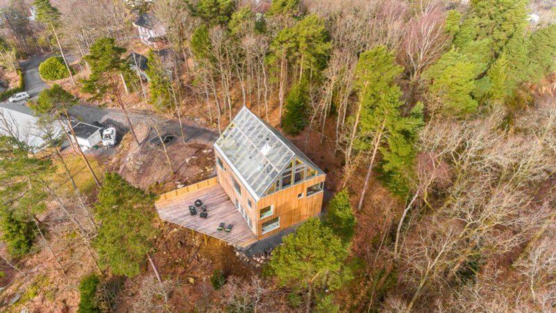 Denna spektakulära och natursköna villa med sin unika glasvåning och lärkfasad ligger mitt i skogen, helt fri från insyn.