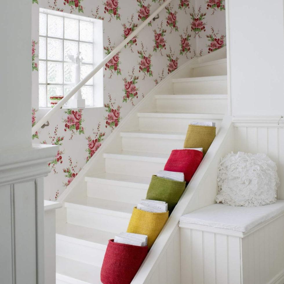 Trappan upp till övervåningen präglas av den härligt blommiga tapeten från Intrade.