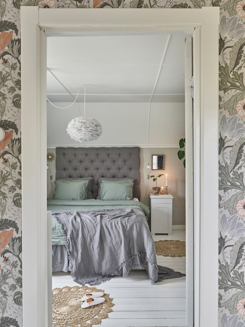 Bakom sänggaveln döljer sig en dörr till en kattvind som rymmer mycket förvaring. Sänggavel, Chilli. Sängkläder och mattor, H&M Home. Lampa, Josephssons i Göteborg. I förgrunden Tapet Anemone, designad av Hanna Wendelbo för Midbec.