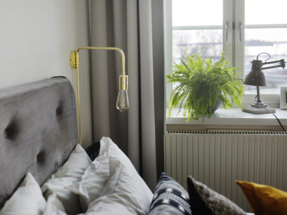 Grön växt. En ormbunke i fönstret ger en härlig känsla i sovrummet. Sänglampan kommer från Mio. Gardinerna är specialbeställda längder från Moderna hem.