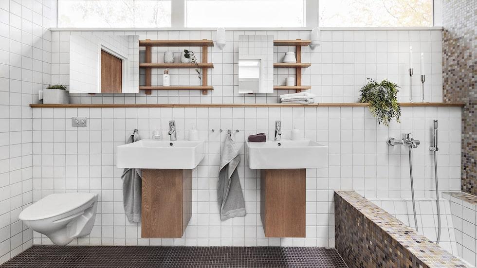 Helkaklat badrum med glasmosaik på golv och på en fondvägg vid badkaret. Golvvärme, platsbyggt badkar, takfönster, downlights i tak, badrumsmöbler i ek och vägghängd wc.