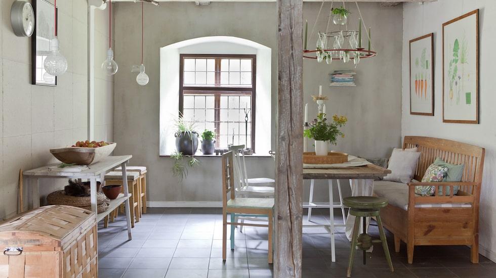 Vid matplatsen har träbockar och en gammal dörr från ladugården blivit ett matbord. Bockar, Ikea. Kökssoffan stod i Maries hem när hon växte upp. Ljuskronan över bordet har hon tillverkat själv.