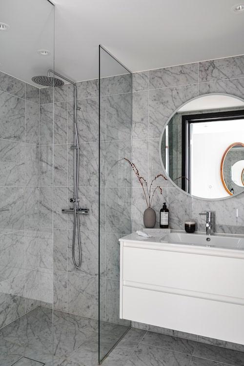 Duschrummet på övervåningen går i ljusare toner än den övriga lägenheten med kvadratiska marmorplattor på väggar och golv. Kommod och duschblandare, Alterna.