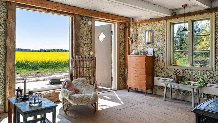 Det charmiga vardagsrummet med trägolv, som går igen i hela huset. Här finns även en kamin.