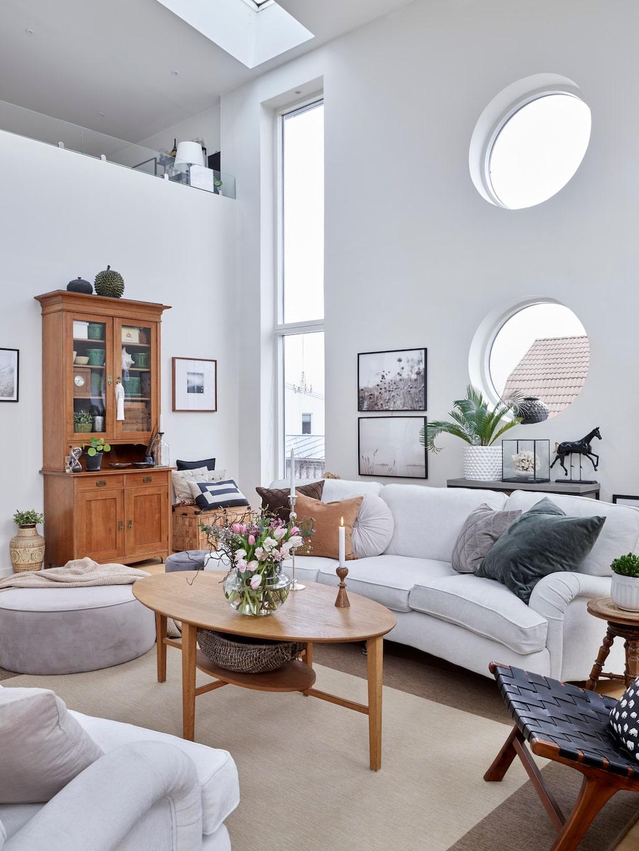 """Allrummets takhöjd är sex meter till nock och här finns olika typer av fönster i både väggar och tak, vilket gör att rummet badar i ljus. Soffor, Mio. Soffbord, Ikea. Det gamla skåpet kallas """"Malins skåp"""" och är ett kärt minne efter en vän."""