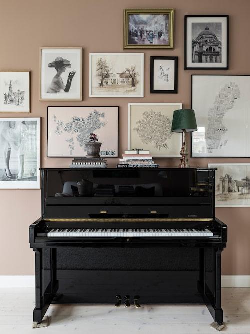 Runt pianot hänger en kul mix av tavlor, allt från foton som Lina tagit till tavlor från Linas föräldrar och fynd från resor. Väggfärgen Blushing Peach från Jotun ger rummet fin värme.