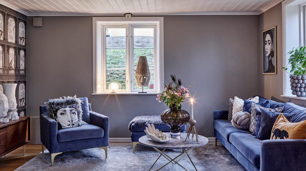 I familjens förra hus var allt vitt, så när de skulle flytta in här var de överens om att ha mer färg. Vardagsrummet har fått mer färg med bland annat blå soffa och fåtölj och en fondvägg i härligt mönster.