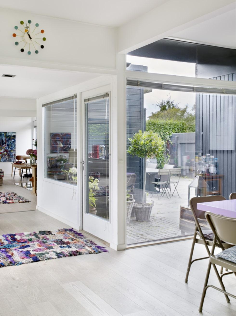 Från köket kommer man ut till terrassen och trädgården genom altandörrar. Fönstren i huset ger rummen ett fantastisk ljus. Mattorna är från Marrakech och klockan är en bröllopsgåva designad av George Nelson.