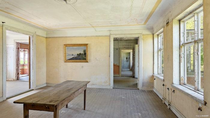 Salen från en annan vinkel. En tavla med guldram hänger ensam kvar på väggen.