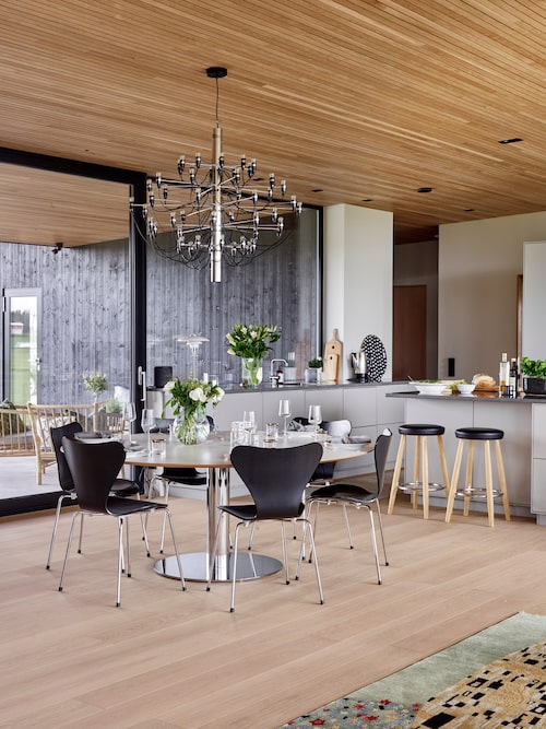 Under senare år har Helén och Thomas kommit att tycka om den avskalade nordiska stilen. Matplatsen är hjärtat i huset med närhet till köket och den öppna spisen. Ljuskrona Sarfatti, Flos. Barpallar, design Hans J Wegner, Carl Hansen. Sjuanstolar, design Arne Jacobsen, Fritz Hansen.