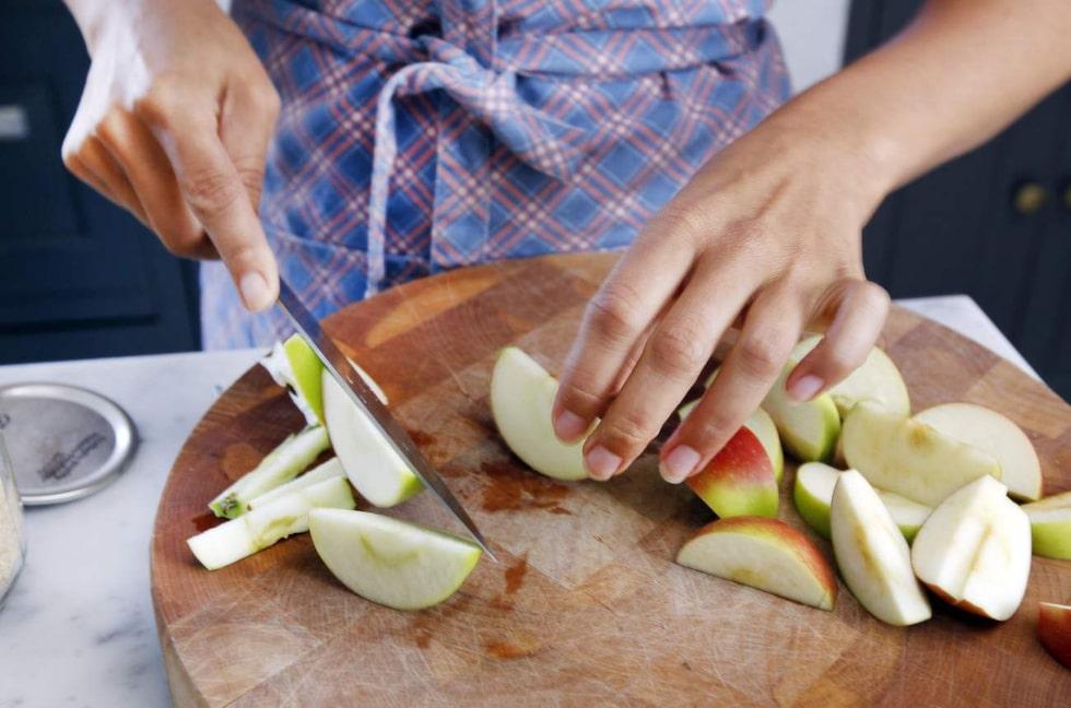 Leila hackar äpplen med van hand.
