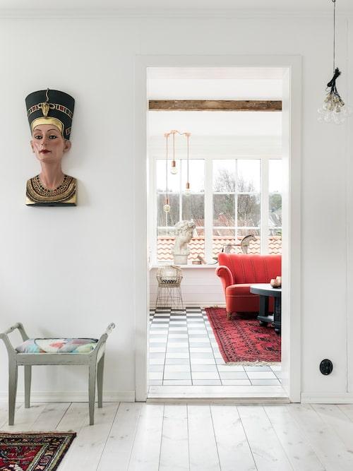 Bysten på väggen föreställer den egyptiska drottningen Nefertiti, ett fynd från en av Göteborgs second hand-affärer. Pallen från 1800-talet har Björn klätt om med tyg designat av Hanna.