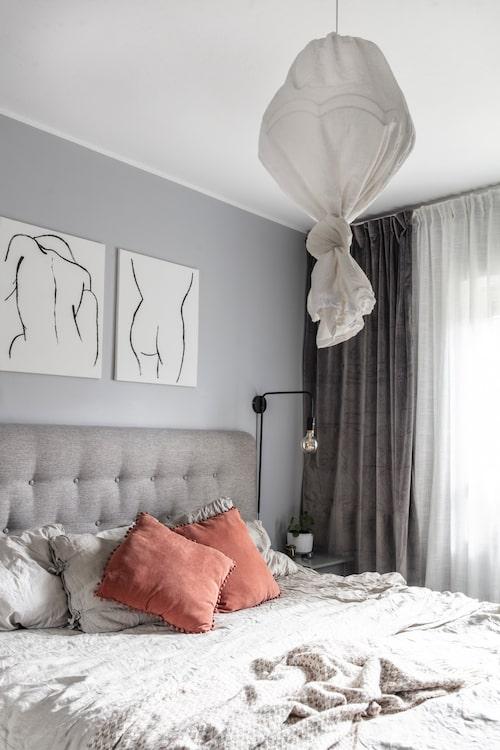 """""""I sovrummet har jag försökt skapa lite hotellkänsla med dubbla gardiner, en stor vadderad sänggavel och matchande nattygsbord och lampor på båda sidor"""", säger Malin. Säng, gavel och sänglampor, Mio. Gardiner, Cellbes. Kuddar, Rusta. Ullpläd, Åhléns. Malin har målat tavlorna och taklampan har hon gjort av en gammal lampskärm och en tunn gardin."""