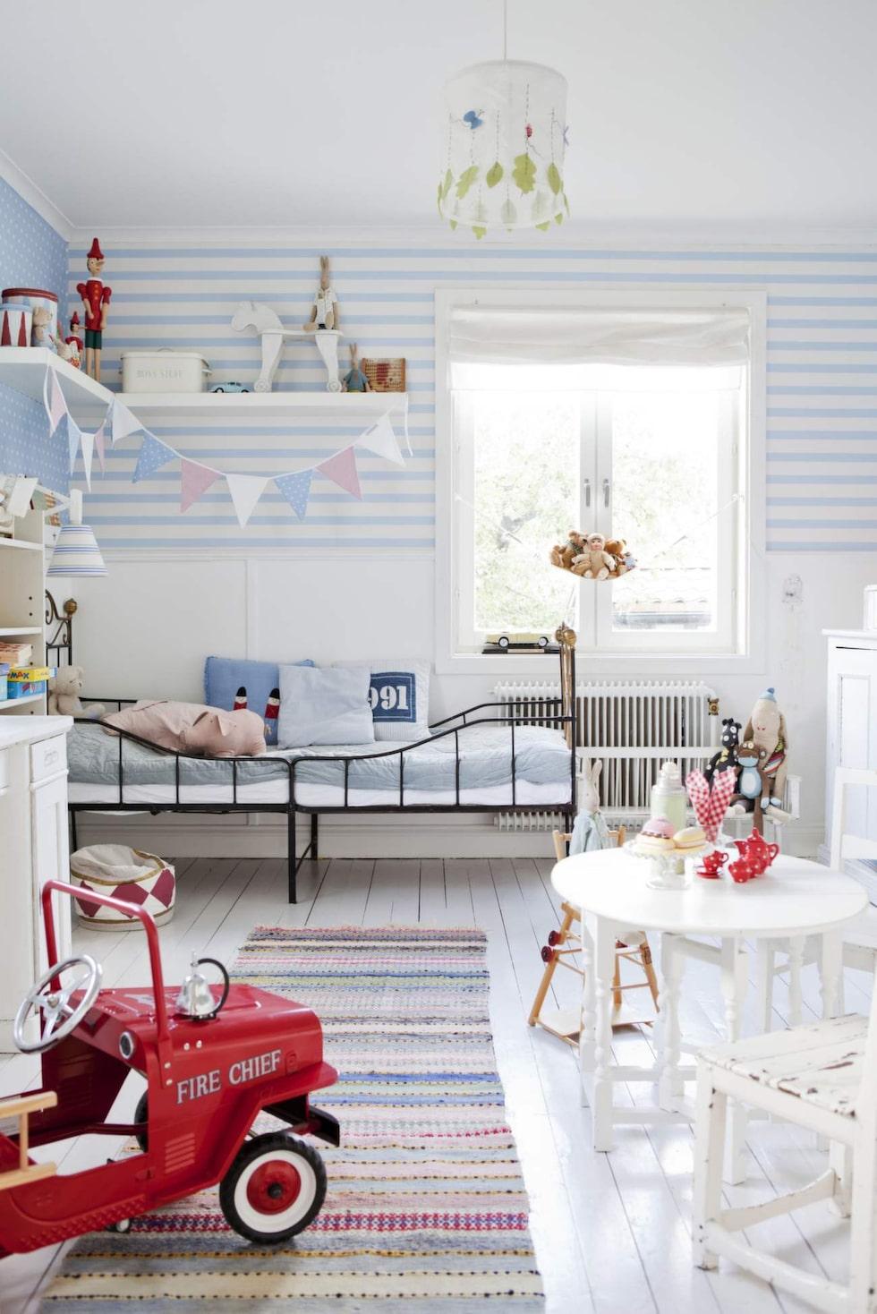 Randigt på väggar och golv. Trasmatta och äldre stålsäng. Stor leksaksbil av plåt är både leksak och prydnad i rummet.