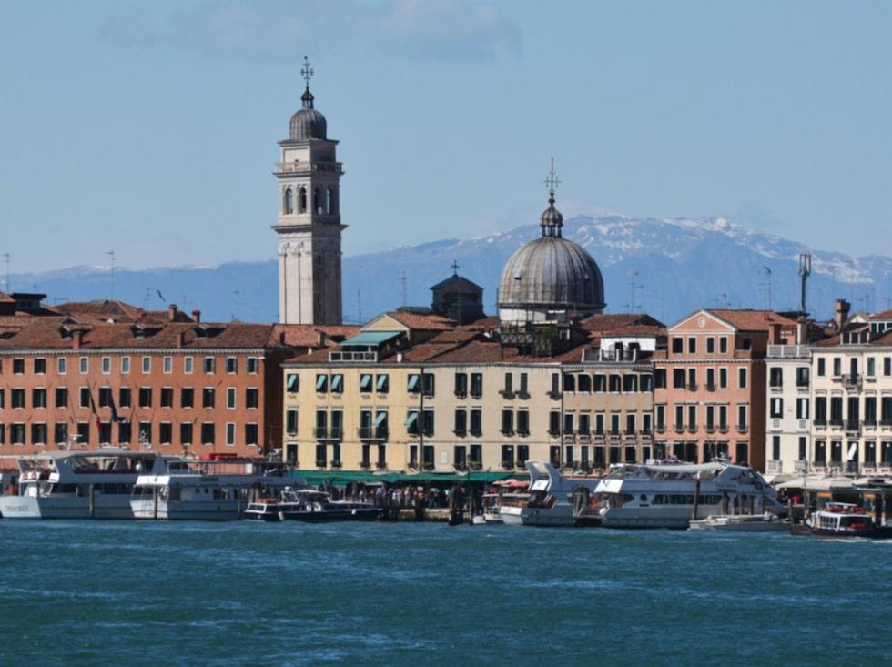 Venedig sett från havet. Ovanför hustaken reser sig alperna i fjärran.